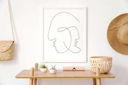 Stijlvol Koreaans interieur van woonkamer met witte mock-up posterframe, elegante accessoires, houten plank en hangende rotan tas en hoed. Minimalistisch concept van woondecoratie. Sjabloon. Lichte kamer. Stockfoto