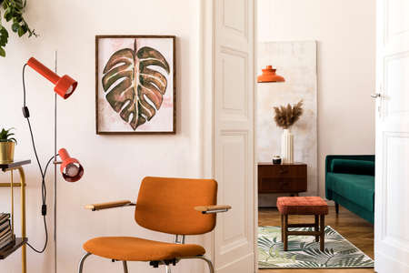 Stylish compositon of retro home interior with mock up poster frame, vintage orange chair, velvet sofa, design lamps, gold shelf, plants and elegant accessories. Nice home decor of living rooms.
