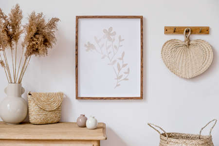 Stylish korean interior of living room with brown mock up poster frame, elegant accessories, flowers in vase, wooden shelf and hanging rattan leaf. Minimalistic concept of home decor. Template. Stockfoto