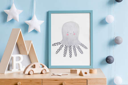 The modern scandinavian newborn baby room with mock up poster frame, wooden toys, mountain box and children accessories. Minimalistic and cozy interior with blue walls. Haniging cotton balls and stars Reklamní fotografie