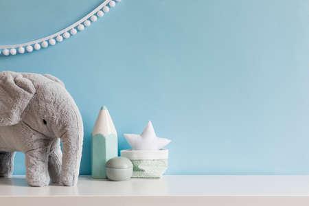 회색 플러시 코끼리, 흰색 별 램프 및 어린이 액세서리가 있는 아늑한 스칸디나비아 신생아실. 파란색 벽과 매달린 흰색 화환이 있는 세련된 인테리어. 주형. 공간을 복사합니다. 스톡 콘텐츠