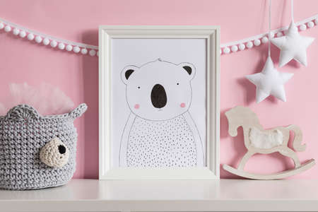 Modern scandinavian newborn baby room with mock up poster frame, rocking horse, cotton bear basket with children accessories. Cozy interior with pink walls. Haniging cotton garland and stars. Template