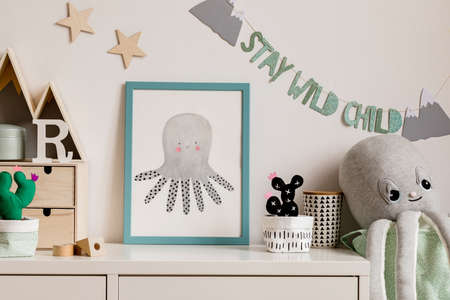 Cozy scandinavian nursery interior with mock up photo frame, plush octopus, cacti and wooden accessories. Hanging stylish inscription and stars on the white background wall. Template. Real photo. Stock Photo