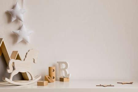 Stijlvolle en gezellige kinderkamer met houten bergkist, speelgoed, hobbelpaard, blokken en hangende witte sterren aan de witte muur. Licht en zonnig interieur. Kopieer ruimte voor inscriptie of product. Sjabloon.