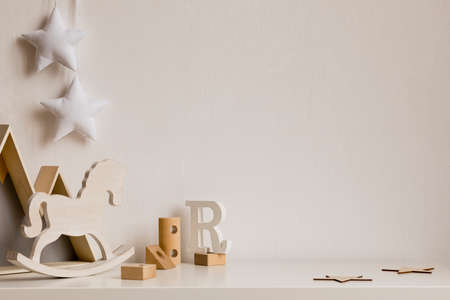 Stylish and cozy childroom with wooden mountain box, toys, rocking horse, blocks and hanging white stars on the white wall. Bright and sunny interior. Copy space for inscription or product. Template.