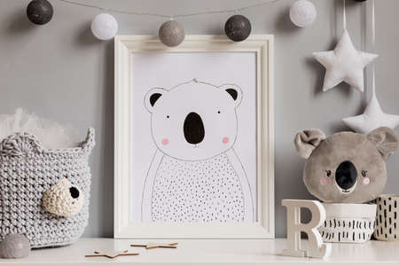 The modern scandinavian newborn baby room with mock up poster frame, koala bear, cotton basket with children accessories. Cozy interior with gray walls. Haniging cotton balls and stars. Template. Archivio Fotografico