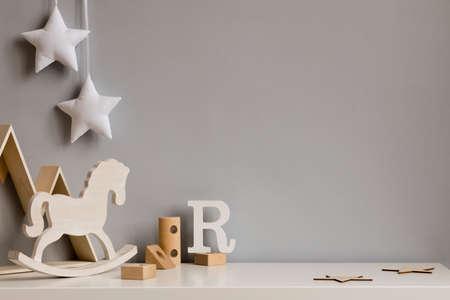 Stilvolles und gemütliches Kinderzimmer mit Holzkiste, Pferd, Blöcken und hängenden weißen Sternen an der grauen Wand. Helles und sonniges Interieur. Platz kopieren. Minimalistisches kindliches Dekor. Vorlage.