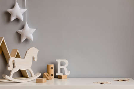 Stylish and cozy childroom with wooden mountain box, horse, blocks and hanging white stars on the gray wall. Bright and sunny interior. Copy space. Minimalistic childish decor. Template. Stock Photo
