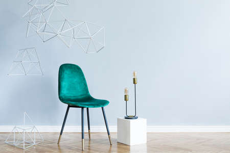 Minimalistic and abstract interior of open space with design green velvet chair, triangle geometric sculptures and lamp. Gray background walls, brown wooden parquet. Modern concept of room. Template.