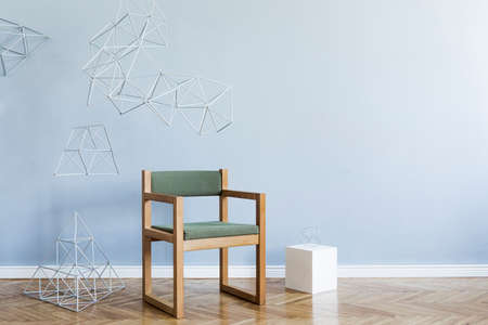 Minimalistic and modern interior of open space with design green armchair, triangle geometric sculptures, white cube. Gray background walls, brown wooden parquet. Abstarct concept of room. Template.