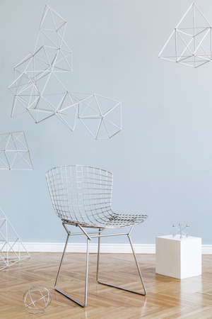 Minimalistic and modern interior of open space with design silver armchair, triangle geometric sculptures, white cube. Gray background walls, brown wooden parquet. Abstarct concept of room. Template.