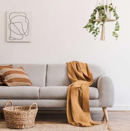 Modern boho-interieur van woonkamer in gezellig appartement met grijze bank, honinggele kussens en plaid, planten, schilderijen, rotanmand en persoonlijke designaccessoires. Stijlvolle woondecoratie. Sjabloon.