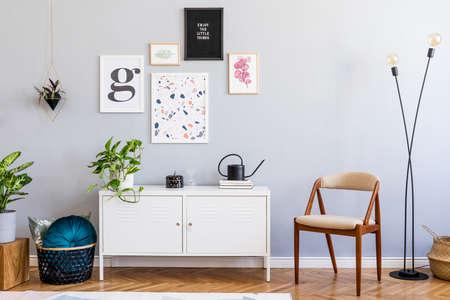 Stijlvol interieur van woonkamer met mock up posters galerijwand, witte plank, design fauteuil, planten, bloemen, lamp en elegante accessoires. Grijze muren als achtergrond. Scandinavische woondecoratie. Sjabloon. Stockfoto