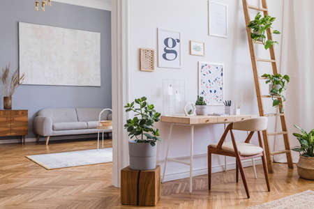 Interni domestici moderni e di design di open space con scrivania in legno, divano, sedia, molte piante, comò, finte cornici per poster e accessori eleganti. Arredamento per la casa elegante e minimalista. Modello.
