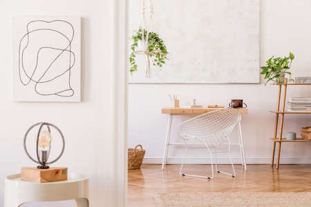 Modern boho interior with design wooden desk, armchair, shelf, white coffee table with lamp, flowers and elegant accessories. Mock up poster frame on the wall. Stylish home decor. Template. Stockfoto