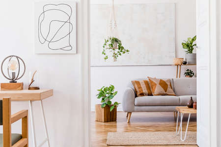 The design boho interior of living room in cozy apartment with stylish coffee table, gray sofa, honey yellow pillows, desk, chair, wooden cube, plants and elegant accessories. Cozy nice home decor.