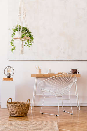 Minimalistic boho interior with design and handmade macrame shelf planter hanger for indoor plants, wooden desk, armchair, lamp, white cube and elegant accessories. Stylish home decor. White walls.