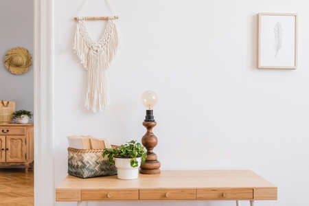 Stylish bohemian interior of living room with wooden desk, beige macrame, design accessories, table lamp, basket with books and mock up photo frame Piece of design woman's room. Design home decor. Stock Photo