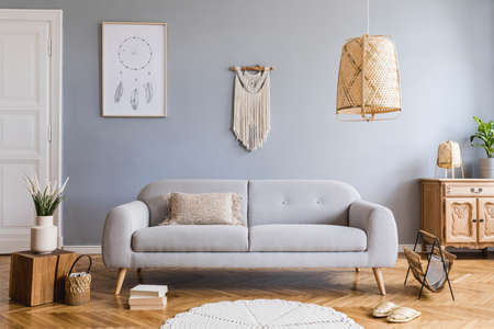 Stylish and design home interior of living room with gray sofa, wooden cube, commode, pillow, macrame, rattan lamp, basket, plants and elegant accessories. Stylish home decor. Template. Mock up poster.