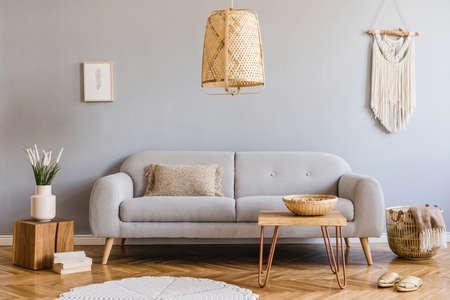 Interni domestici minimalisti e di design del soggiorno con divano grigio, cubo di legno, tavolino, cuscino, macramè beige, cornice per poster finta e accessori eleganti. Arredamento elegante per la casa. Modello.