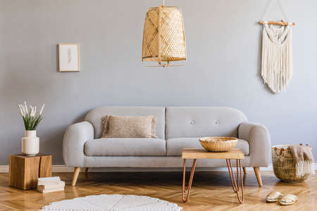 Minimalistyczne i designerskie wnętrze salonu z szarą sofą, drewnianą kostką, stolikiem kawowym, poduszką, beżową makramą, makietą ramy plakatowej i eleganckimi dodatkami. Stylowy wystrój domu. Szablon.