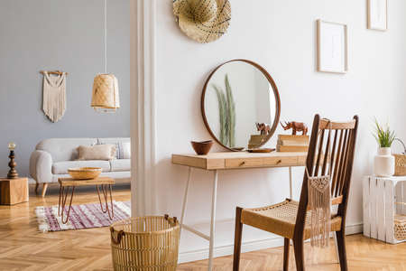 Design bohemian interior of open space at apartment with stylish chair, wooden desk, mirror, sofa, coffe table, basket and elegant accessories. Stylish boho home decor. Template Bright and sunny space.