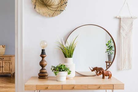 Intérieurs boho ensoleillés de l'appartement avec miroir, coiffeuse, lampe de table, fleurs, plantes, chapeau en rotin, sculpture, macramé et accessoires design. Décor à la maison élégant d'espace ouvert. Modèle. Banque d'images