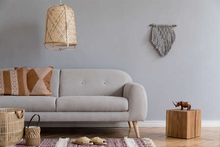 Stylish and design home interior of living room with gray sofa, wooden cube, pillows, rattan lamp and basket, gray macrame, carpet and elegant accessories. Stylish home decor. Template. Gray walls.
