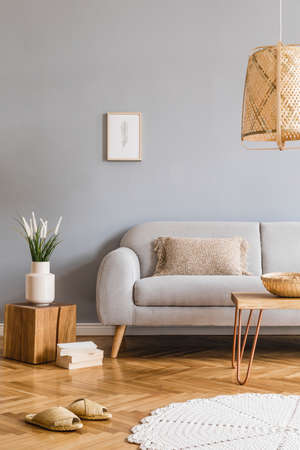 Minimalistic design home interior of living room with gray sofa, wooden coffee table, photo frame, flowers, rattan lamp, basket and elegant accessories. Stylish home decor. Template. Gray walls. Stock Photo