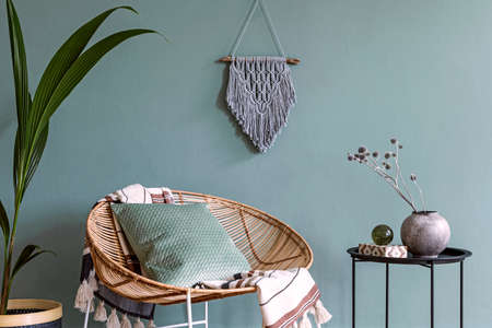 Stylish minimalistic interior of living room with design rattan armchair, black coffee table, tropical plant in basket, graymacrame on the wall and elegant accessories. Eucalyptus color of wall.