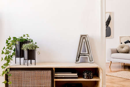 Modern scandinavian home interior with design wooden commode, plants in black pots, cement letter, gray sofa, books and personal accessories. Stylish home decor. Template. Copy space. White walls.
