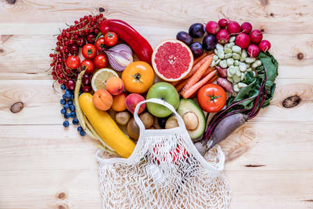 Modern composition of fresh healthy vegetables and fruits on the wooden table in the kitchen. Healthy detox and balance diet. Lifestyle. Vegetarian vegan background. Zero waste. Top view. Copy space. Stock Photo
