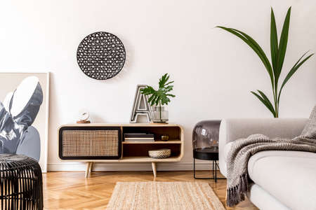 Stylish scandinavian living room interior with gray sofa, black lamp, design commode, tropical plants, sculpture, books and personal accessories. Modern home decor. Template. Rattan decoration.