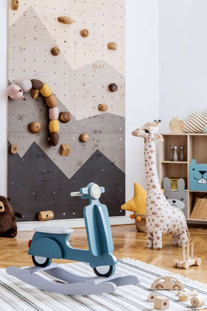 Scandinavian interior design of playroom with modern climbing wall for kids, design furnitures, kid's motor toy, soft toys, teddy bear and cute children's accessories. Stylish kidroom decor. Template.