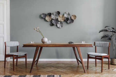 Modern and stylish dining room interior with glamor wooden table, elegant chairs and design decoration. Template. Home decor. Gray background wall. Minimalistic concept of interior design.