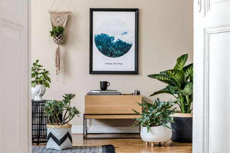 Modern scandinavian living room interior with black mock up poster frame, design commode, a lot of plants in different pots, macrame and elegant accessories. Template. Stylish home decor.