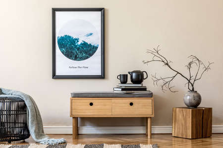 Stylish scandinavian living room interior with modern wooden commode, rattan basket, vase with flower, tea pot and elegant personal accessories. Mock up poster frame on the beige wall. Template.