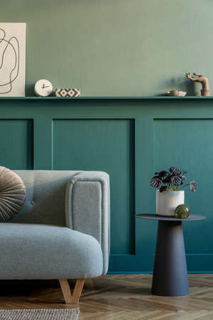 Modern interior of living room with mint sofa, coffee table, plant in pot and elegant personal accessories. Mock up poster frame. Stylish home decor. Green wooden paneling with shelf. Template. Archivio Fotografico