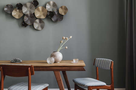 Modern and stylish dining room interior with glamor wooden table, elegant chairs and design decoration. Template. Home decor. Gray background wall. Standard-Bild