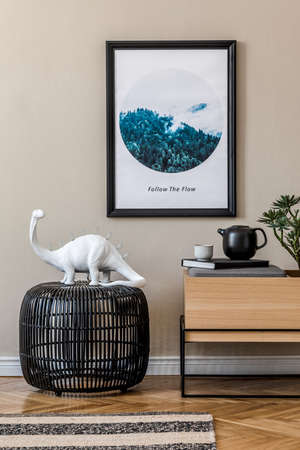 Stylish scandinavian living room interior with modern wooden commode, black rattan basket, table lamp, tropical plant and elegant personal accessories. Mock up photo frame on the wall. Template.