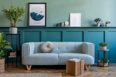 Stylish interior of living room with mint sofa, design furnitures, plants, pillow and elegant accessories. Green wood paneling with shelf. Modern home decor. Mock up poster frames. Template.
