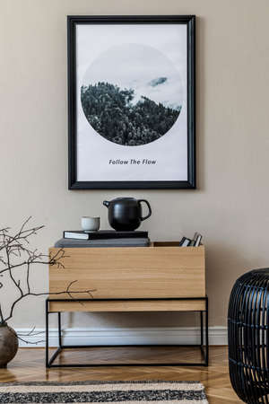Modern scandinavian living room interior with black mock up poster frame, design commode, leaf in vase, black rattan basket, books and elegant accessories. Template. Stylish home decor.