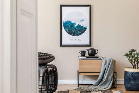 Modern scandinavian living room interior with black mock up poster frame, design commode, rattan basket with plants, books, tea pot and elegant accessories. Template. Stylish home staging. Japandi. Standard-Bild