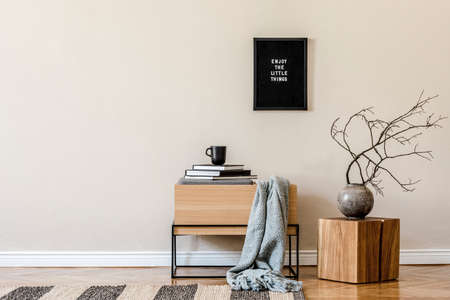 Modern scandinavian living room interior with mock up poster frame, design wooden commode, tea pot, wooden cube, flowers and elegant accessories. Beige concept. Stylish home decor. Ready to use.