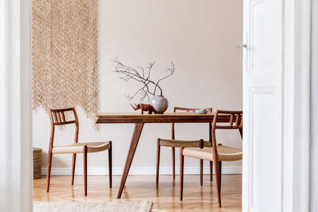 Stylish and beige interior of dining room with design wooden table and chairs, vase with flowers, sculpture, elegant and rattan accessories. Korean style of home decor. Wooden parquet. Template.