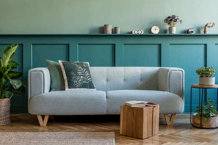 Stylish interior of living room with mint sofa, design furnitures, plants, pillow and elegant accessories. Green wood paneling with shelf. Modern home decor. Copy space. Template.
