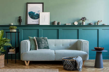 Stylish interior design of living room at apartment with mint sofa, plants, design furnitures and elegant accessories. Mock up poster frames on the shelf. Green wood paneling. Home staging. Template. Standard-Bild