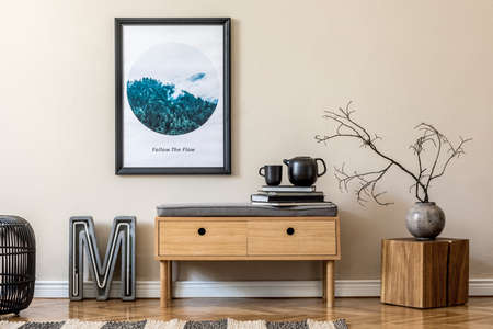 Design scandinavian home interior of living room with wooden commode, modern neon, rattan pouf, vase with flowers, tea pot and elegant accessories. Stylish home decor. Template. Mock up poster frame.