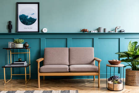 Stylish interior of living room with brown wooden sofa, design furnitures, plants, pillow and elegant accessories. Green wood paneling with shelf. Modern home decor. Interior design. Template.