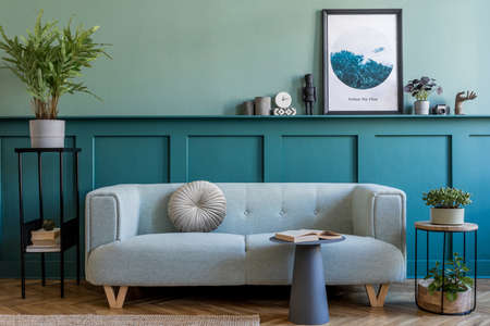 Stylish interior of living room with mint sofa, design furnitures, plants, pillow and elegant accessories. Green wood paneling with shelf. Modern home decor. Mock up poster frame. Template.